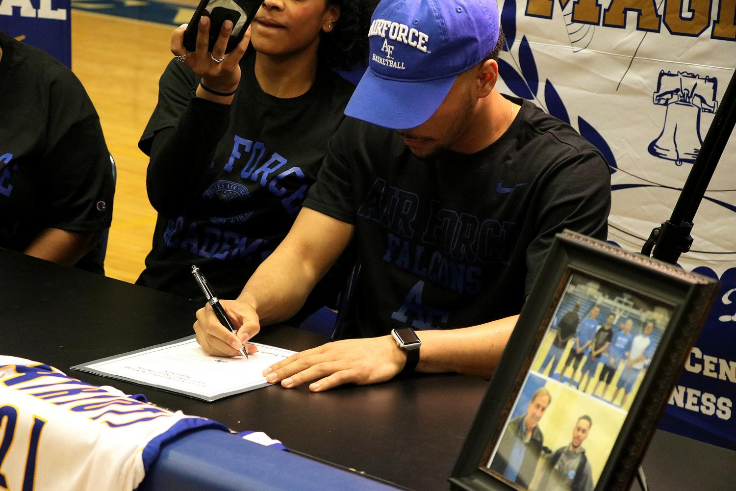 Nicolas René signs his contract with the United States Air Force Academy.