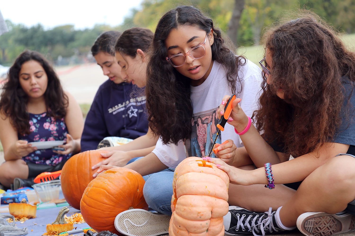 Freshman Danielle Pointer, junior Helen Velasquez, sophomore Rachel Velasquez, junior Leah Coreas and junior Aabha Kc carve their pumpkins at the WRIOT Pumpkin Carving Social.