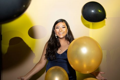 Senior Jessica Mendoza stands with the black and gold balloons around her.