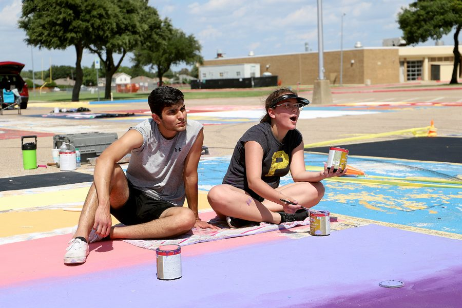Senior Kaylee Alanis paints her parking space with friends.