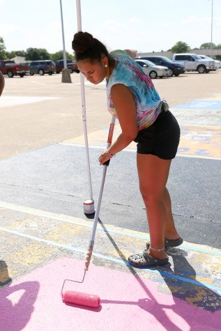 Senior Malaya Samuel paints her parking spot.